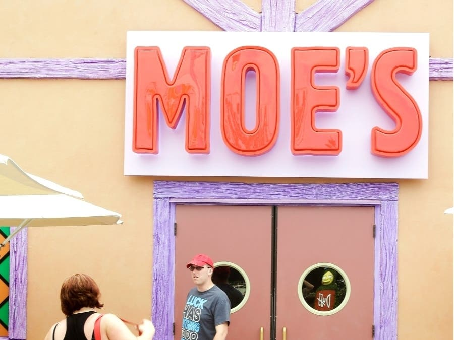 """In this Sept. 5, 2013 photo, guests snap photos at the entrance to Moe's Tavern in """"The Simpson's"""" themed Springfield USA at Universal Orlando in Orlando, Fla."""