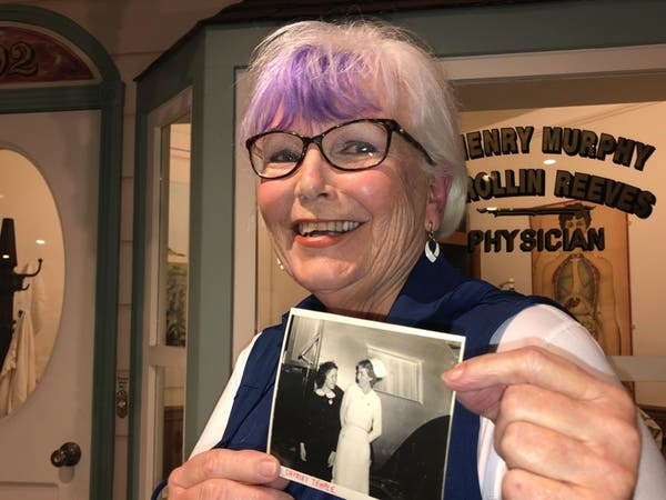 Nurse practitioner Sigrid Stokes, 76, holds a photograph of her mother talking to Shirley Temple, at the Salinas Valley Memorial Hospital in Salinas, Calif., Wednesday, Feb. 3, 2021.