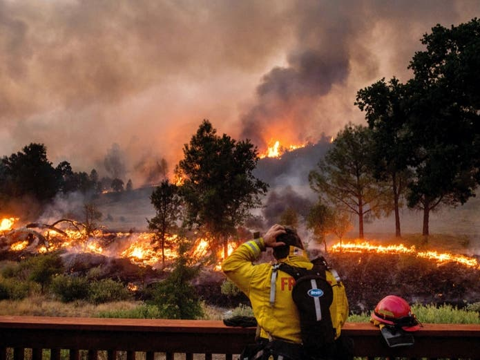 A firefighter rubs his head while watching the LNU Lightning Complex fires spread through the Berryessa Estates neighborhood of unincorporated Napa County, Calif., on Friday, Aug. 21, 2020. The blaze forced thousands to flee and destroyed hundreds of home