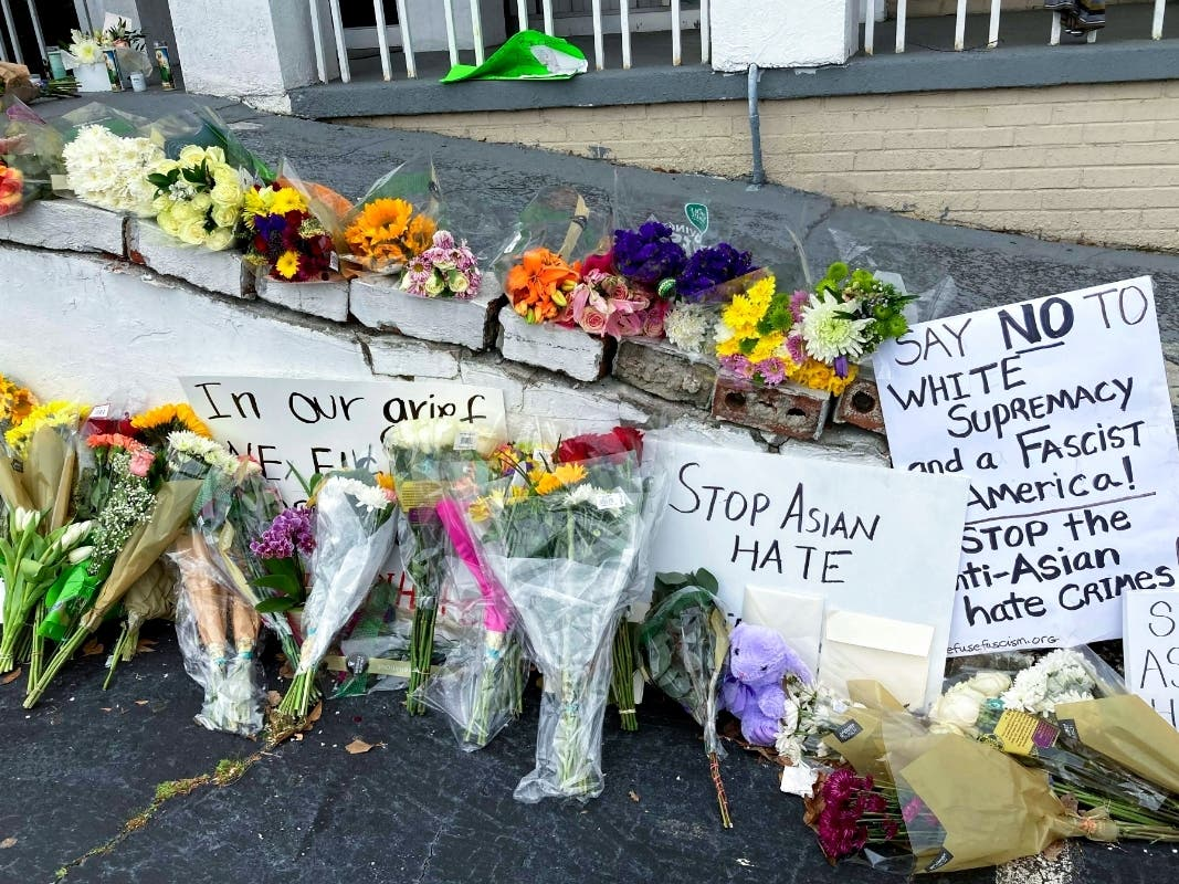 This March 19 file photo of flowers, candles and signs are displayed at an Atlanta memorial, following the shooting by Robert Aaron Long, a white man charged with a hate crime and accused of shooting and killing six women of Asian descent and two others.