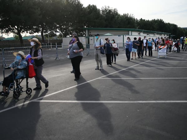ANAHEIM, CALIFORNIA - JANUARY 13: People wait in line to receive the COVID-19 vaccine at a mass vaccination site in a parking lot for Disneyland Resort on January 13, 2021 in Anaheim, California.
