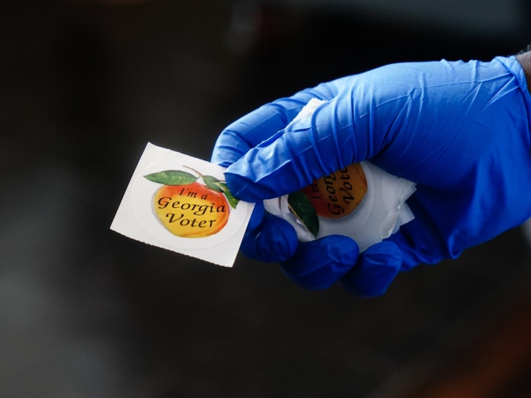 """A polling place worker holds an """"I'm a Georgia Voter"""" sticker to hand to a voter on June 9, 2020 in Atlanta, Georgia."""