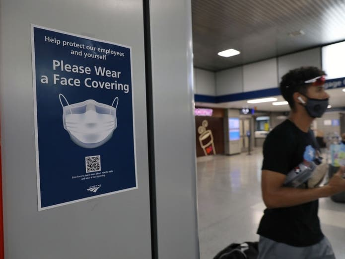 People walk through Pennsylvania Station as city workers attempt to hand out information sheets to travelers arriving by train.