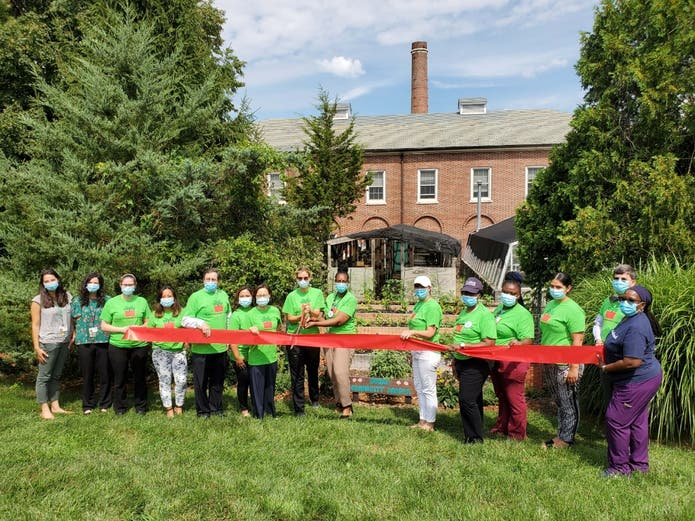 Pictured at the Community Garden Ribbon Cutting are: Burke Rehabilitation Hospital President and CEO Jeffrey Menkes (5th from left) and Burke Senior VP and Chief Medical Officer Mooyeon Oh-Park, MD (7th from left), along with volunteer employees