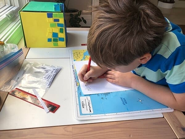A Montessori child chooses independent geography work using simple, screen-free materials at home.