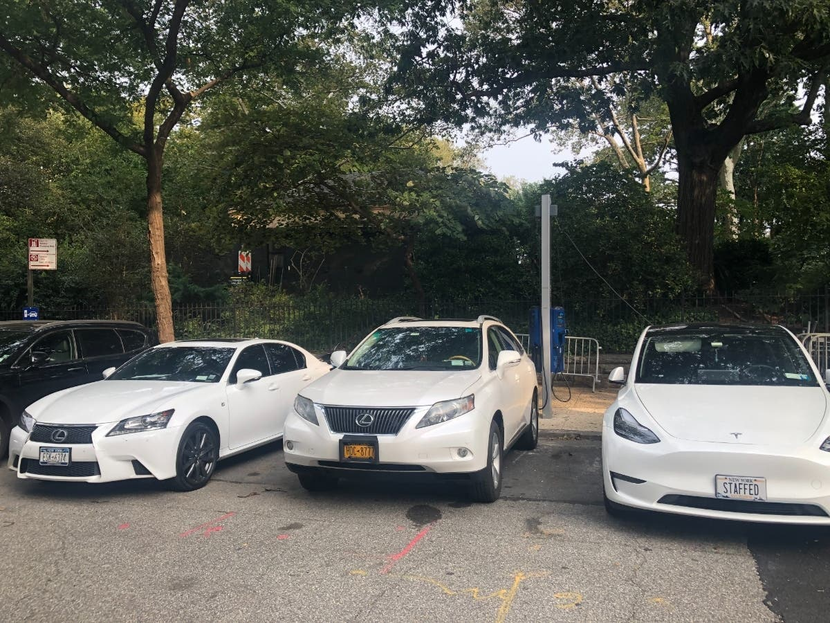 Two gas-powered cars obstruct the brand new electric vehicle charger on East End Avenue near East 87th Street on Tuesday, joined by a single electric vehicle at right.