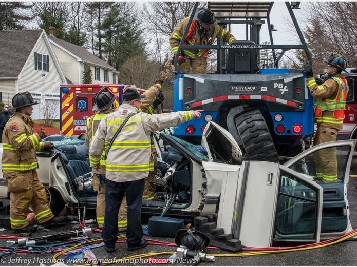 FIre and EMS crews worked to extricate a woman from a vehicle which went under a tractor-trailor