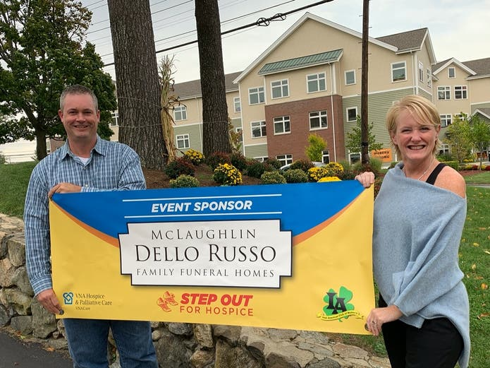 Brian Kelley and Jamie Kelley, co-chairs of the Woburn Friends of VNA Hospice & Palliative Care, unveil a banner in gratitude of Dello Russo Family Funeral Home's sponsorship of Step Out for Hospice.