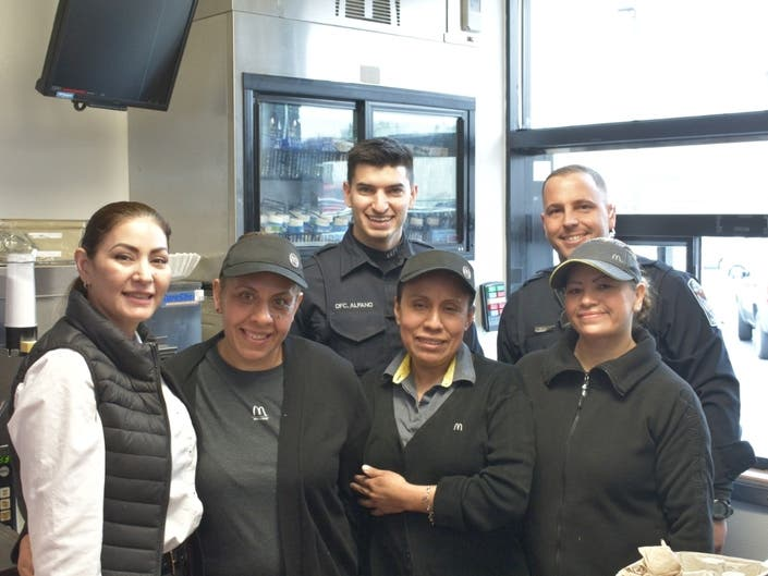 Police Officers work alongside the Crystal lake McDonald's employeesserving coffee to the customers